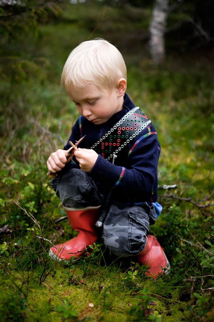 Pojke med knivbälte i skogen